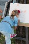 dievčatko maľuje kriedov na papier