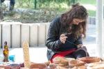 mladé dievča vyšíva v parku na látku