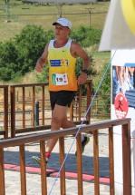 bežec v žltom drese prebieha cieľom