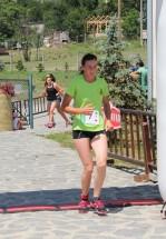 dievča v zelenom drese dobieha do cieľa