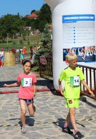 chlapec a dievča prebehujú cieľom
