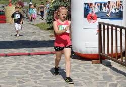 dievča v červenom prebehuje cieľom