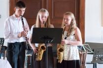 trojica hrá na dychové nástroje