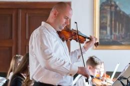 chlap hrá na husliach