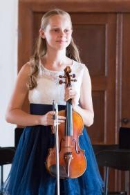 dievča drží husle v rukách