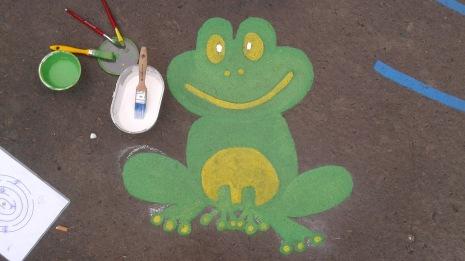 zelená žaba namaľovaná na chodníku