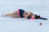 mladá krasokorčuliarka leží na ľadovej ploche