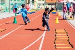 chlapec beží po tartanovej dráhe