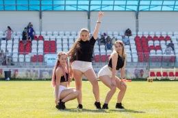 tri mladé dievčatá tancujú na trávnatej ploche
